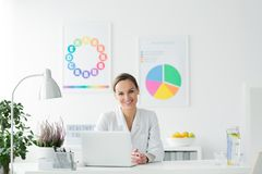 Happy dietician in the office stock images