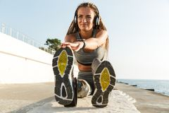 Happy disabled athlete woman with prosthetic leg. Doing stretching exercises while sitting at the beach and listening to music with headphones royalty free stock images