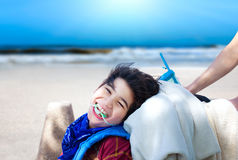 Happy disabled boy being pushed in wheelchair with ocean beach i Royalty Free Stock Photography