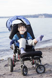 Happy disabled boy in wheelchair on the beach Royalty Free Stock Photo
