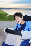 Happy disabled boy  in wheelchair by lake at dusk Royalty Free Stock Photo