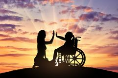 Happy disabled child girl in wheelchair and her mom on a walk stock photos