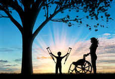 Happy disabled Child is invalid with crutches beside wheelchair and nurse near tree Stock Images