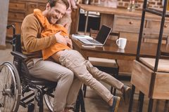 Happy disabled father in wheelchair hugging with cute little son. At home stock photos