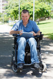 Happy disabled man. Using tablet at the park Royalty Free Stock Images