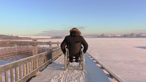Happy disabled man on wheelchair near lake in winter stock video footage