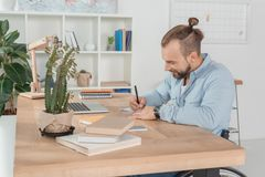 Disabled man writing in notebook. Happy disabled man on wheelchair writing in notebook at workplace royalty free stock image