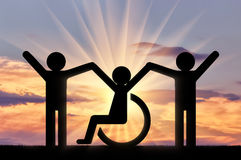 Happy disabled person in a wheelchair together with healthy people. Concept of social assistance royalty free stock photos