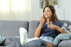 Happy disabled woman taking a painkiller pill. Sitting on a couch in the living room at home Royalty Free Stock Photo