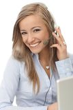 Happy dispatcher at work. Happy blonde dispatcher working, using headphones, smiling Stock Photo