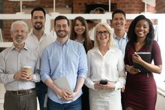 Happy diverse business team standing in office looking at camera