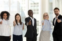 Happy diverse businesspeople standing looking at camera showing thumbs up royalty free stock images