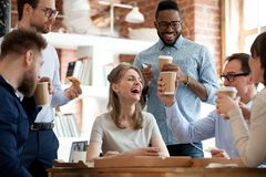 Happy diverse colleagues celebrate during lunch break in office. Happy diverse colleagues have fun at lunch break in office, smiling multiracial employees laugh stock photo
