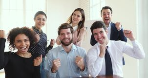 Happy diverse employees group celebrate corporate success look at camera