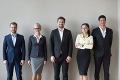 Happy diverse executives team standing near wall headshot portrait stock photography