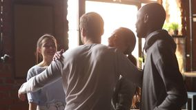 Happy diverse friends embrace greeting male buddy coming at meeting. In cafe, multi ethnic mates group hugging guy laughing give fist bump say hello, students stock footage
