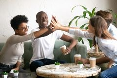 Happy diverse friends giving high five together in cafe royalty free stock image