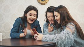 Happy diverse friends using phone together in cafe during lunch. Looking at smartphone screen. Laughing man showing. Funny video in social network. Online joke stock video footage