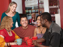 Happy Diverse Group of Adults. Smiling diverse group of mature adults in cafe Stock Photo