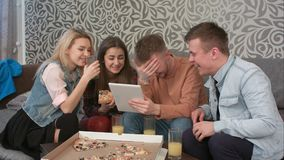 Happy diverse group of friends laughing at what they see on the screen of a computer tablet stock image