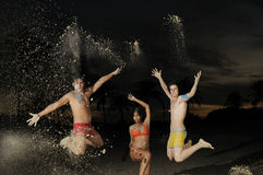Happy diverse group jumping. Multiracial group of friends jumping on the beach Stock Image