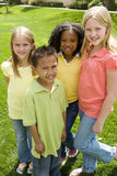 Happy diverse group of kids outside at a park. Diverse group of kids smiling outside at a park Royalty Free Stock Photography