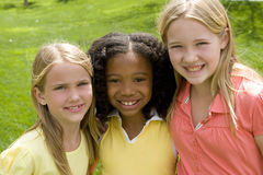Happy diverse group of little girls. Diverse group of girls smiling outside at the park Stock Images