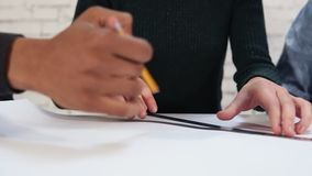 Happy diverse group of students or young business team working on project.: they are drawing a plan using pencil and. Ruler. Camera shows hands then moves back stock footage