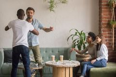 Happy diverse male friends greeting at reunion meeting in cafe stock images