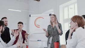 Happy diverse office colleagues cooperate, discuss work at creative healthy workplace team meeting slow motion RED EPIC. Multiethnic business people work as a stock video