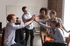Happy diverse office employees group give high-five, corporate trust concept