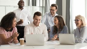 Happy diverse office workers team laughing together at group meeting