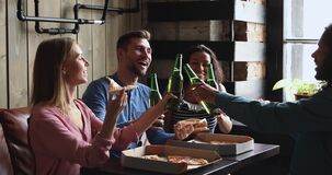 Happy diverse young friends eating pizza drinking beer clinking bottles