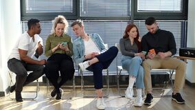 Happy diverse young diverse multiethnic men and women sharing social media news using mobile gadgets.
