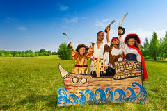 Happy diversity children as pirates with swords. Happy diversity group of children in pirate costumes with swords standing behind ship made of cardboard Stock Images