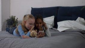 Diversity girls listening to music on smart phone stock footage