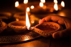 Happy diwali - Hand holding or lighting or arranging diwali diya or clay lamp royalty free stock photo