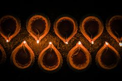Happy Diwali - many Terracotta diya or oil lamps arranged over clay surface or ground in one line or curved or zigzag form, select. Ive focus stock image