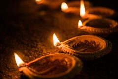 Happy Diwali - many Terracotta diya or oil lamps arranged over clay surface or ground in one line or curved or zigzag form, select. Ive focus stock photo