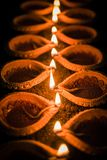 Happy Diwali - many Terracotta diya or oil lamps arranged over clay surface or ground in one line or curved or zigzag form, select. Ive focus royalty free stock photo