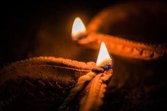 Happy Diwali - Terracotta diya or oil lamps over clay. Surface or ground, selective focus