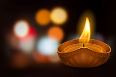 Happy Diwali. Vector illustration of burning oil lamp diya on Diwali Holiday, ancient Hindu festival of lights, on blurred background. There is a space for your Royalty Free Stock Image
