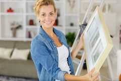 Happy diy woman renewing frame at home. Woman royalty free stock image