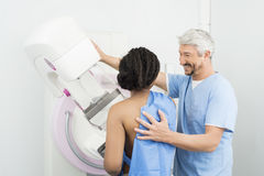Happy Doctor Assisting Patient Undergoing Mammogram Test royalty free stock photos