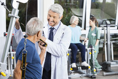 Happy Doctor Assisting Senior Man With Resistance Band Royalty Free Stock Photo