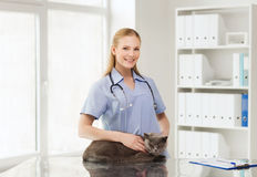 Happy doctor with cat at vet clinic Royalty Free Stock Images