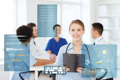 Happy doctor with clipboard at hospital. Medicine, healthcare, technology and people concept - happy female doctor with clipboard over group of medics meeting at Royalty Free Stock Image