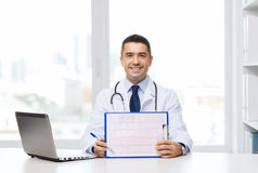 Happy doctor with clipboard and laptop in office Stock Images