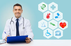Happy doctor with clipboard and medical icons. Medicine, profession, technology and people concept - happy male doctor with clipboard and stethoscope over blue Royalty Free Stock Photo