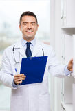 Happy doctor with clipboard in medical office Stock Photos